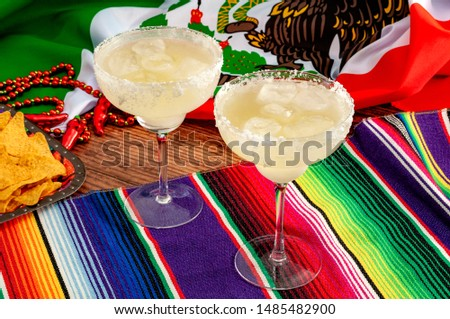 Mixed alcoholic drinks and spirits, patriotic party and mexican fiesta concept theme with two margarita glasses with salted rim, tortilla chips and the flag of Mexico on traditional rug called serape #1485482900