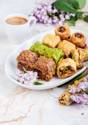Mixed  baklava in white plate on marble background. Ramadan food, turkish arabian cuisine. Selective focus
