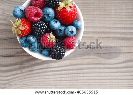 Mixed berries in plate on rustic wooden background. Close up, top view, high resolution product. Copy space. Harvest concept. #405635515