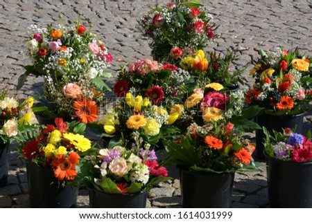 mixed bunches of spring flowers in basket outdoors, bouquet of different flowers selling in a market on paving stones