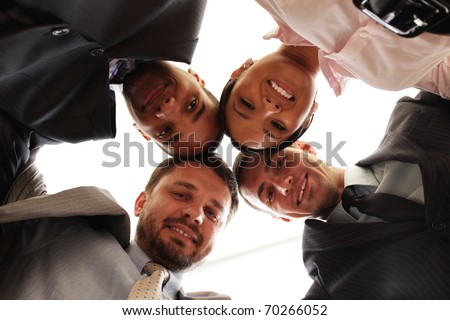Mixed businessteam with heads together over white