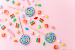 Mixed collection of colorful candy, on pink background. Flat lay, top view