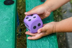 Mixed color dices in child's hands. Board games for kids. Winner consept