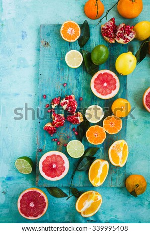 Mixed festive colorful tropical and citrus fruit sliced with leaves over light blue tabletop. Pastel rustic style.