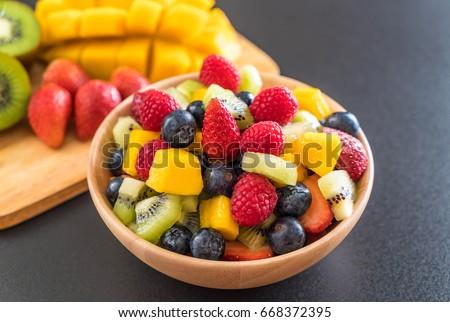 mixed fresh fruits (strawberry, raspberry, blueberry, kiwi, mango) on wood bowl Stock photo ©