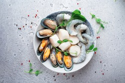 Mixed frozen seafood in plate on a gray stone background. Raw Shrimp, mussels and scallops