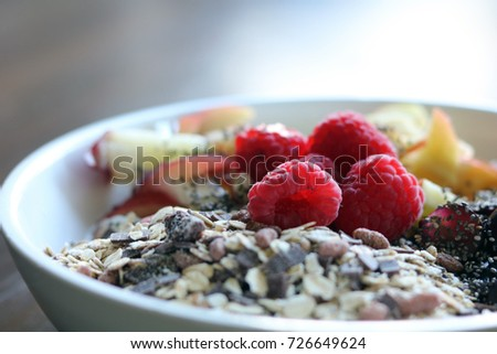 mixed fruit and cereal in a white bowl on brown wooden table