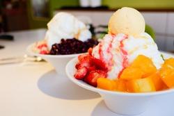 Mixed Fruit Bingsu. A bowl of milk shaved ice served with fresh fruits. Strawberry, Kiwi and Mango