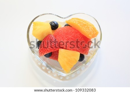 Mixed fruit on heart shape glass bowl with copy space