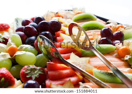 Mixed fruit platter with tongs in sunlight - stock photo