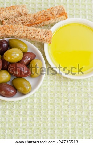 Mixed green and black olives, extra virgin olive oil on white plates, toasted bread - traditional Mediterranean appetizer. Selective focus.