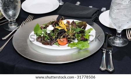 Mixed green salad on silver platter and elegant table setting
