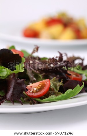 Mixed greens with cherry tomatoes sprinkled with sesame seeds. Shallow DOF