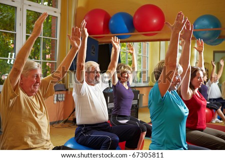 Mixed group doing back exercises in a gym - stock photo