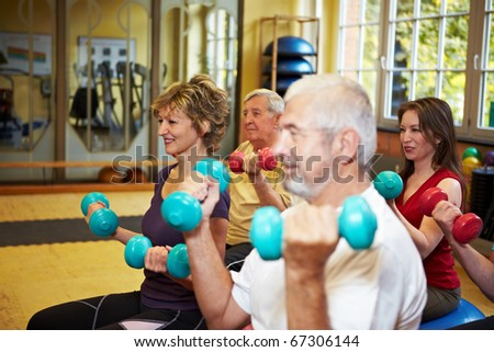 Mixed group doing dumbbell exercises in a gym