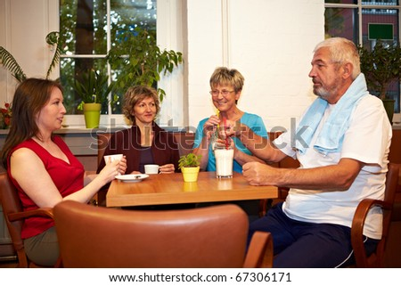 Mixed group drinking coffee in a gym