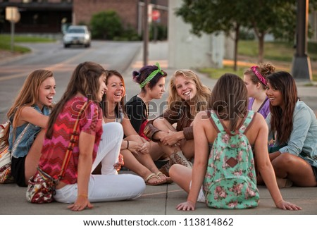 Mixed group of 8 female students sitting on the ground