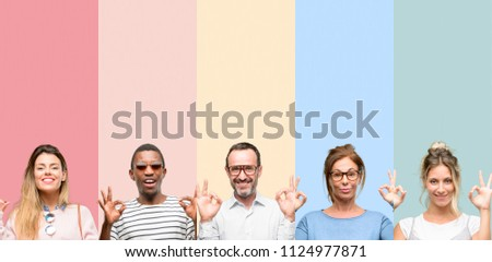 Mixed group of people, women and men doing ok sign gesture with both hands expressing meditation and relaxation