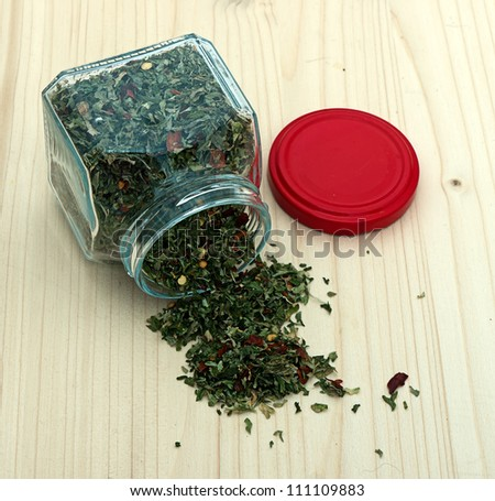 Mixed herbs with jar on wooden board