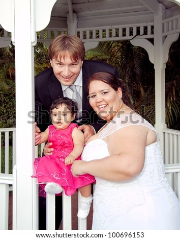 Mixed Hispanic and Caucasian newlywed couple on their wedding day with their baby girl