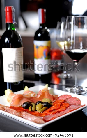 mixed italian antipasti on a plate with wine