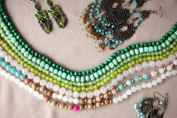 Mixed jewelery on grey cotton background: beads, earrings, rings, glass beads, necklace chain (ethnic, turkish adornment in blue, grey and green colors)