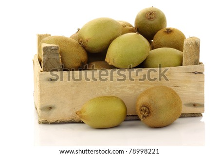 mixed kiwi fruit in a wooden crate on a white background
