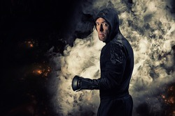 Mixed martial artist goes to battle in a sweatshirt amid fire and smoke. Concept of mma, ufc, thai boxing, classic boxing. Mixed media
