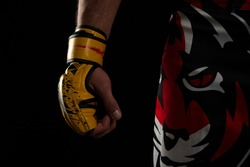 Mixed martial arts (MMA) fighter. Detail of the yellow glove with tiger pants on black background. Mixed martial arts concept.
