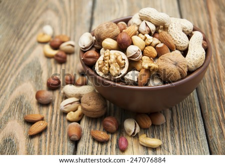 Mixed nuts in a bowl on a wooden background  #247076884