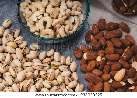 mixed nuts in ceramic bowls, wooden spoon. Almonds, walnuts, cashew nuts, pistachio nuts