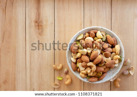 mixed nuts in white ceramic bowl on wooden background.