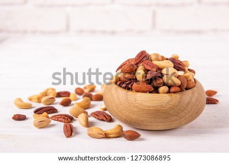 Mixed nuts in wooden bowl and scattered on table. Trail mix of pecan, almond, macadamia & brazil edible nuts with walnut hazelnut on wood textured surface. Background, copy space, top view, close up.