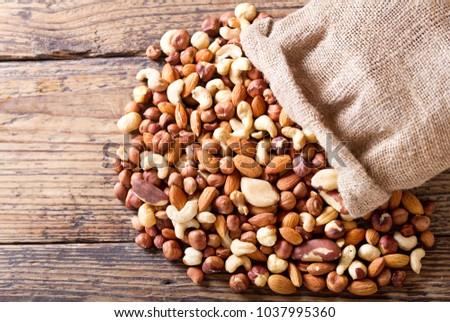 mixed nuts on a wooden table, top view