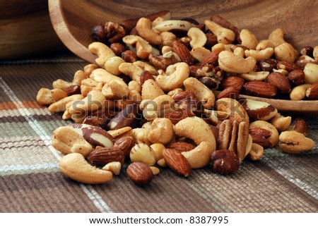 Mixed nuts spilling out of a wooden bowl onto color coordinated placemat.  Macro still-life with shallow dof