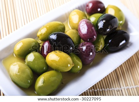 Mixed olives in oil on a plate