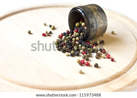 Mixed pepper in metallic bowl on wooden background. Selective focus.