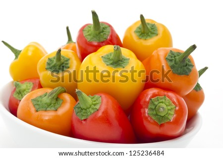 Mixed Peppers in white plate on white background - closeup