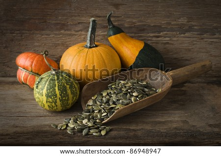 Mixed pumpkins and seeds on wooden background close up