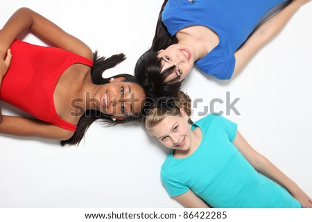 Mixed race african american, oriental Japanese and blonde caucasian teenage school student girl friends lying on floor in fun pose looking up with big smiles.