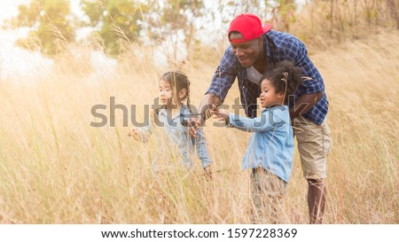 Mixed race African family, dad with two adorable diverse daughters, thai and african enjoy the countryside. Countryside camping for kindergarten to learn about nature and environment.