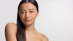 mixed race asian model in studio beauty shoot Model poses to a camera, straight hair combed to right side. Ideal skni and no makeup makeup Head and shoulders crop Watching to the camera