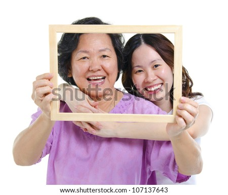 Mixed race Asian senior mother and adult daughter looking fun through an empty frame