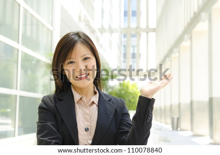 Mixed race Asian woman showing welcome sign over modern building