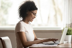 Mixed race attractive woman wearing glasses look at pc screen typing business letter informal e-mail chatting with friend online, african female freelancer sitting at table working on computer at home