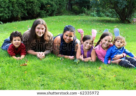 Mixed race beautiful ethnic family with parents and four children laying on the grass