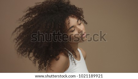 mixed race black woman portrait with big afro hair, curly hair in beige background dancing and jumping with hair flying in air