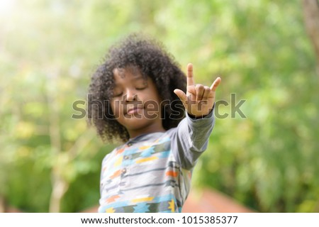 Mixed race boy show I love you sign language . kids ,childhood love concept . selective focus at finger  .