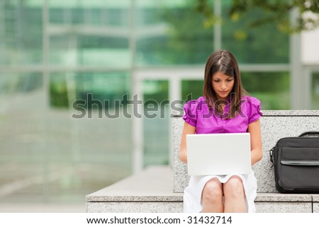 mixed-race business woman using laptop computer outdoors. Copy space
