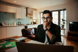 Mixed race businessman seated concentrating while working on laptop sitting at home office
